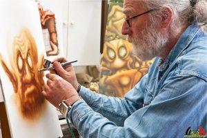 Tekenaar Johannes Desseyn aan het airbrushen